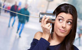 Portrait of young woman hearing through a tin can at city — ストック写真