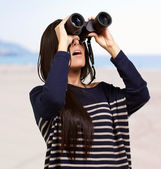 Portrait of young woman looking through a binoculars against a b — Stock Photo