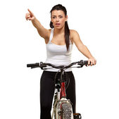 Young girl sitting on bicycle pointing — Stockfoto