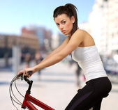 Portrait of young woman cycling at city — Stock Photo