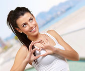 Portrait of young woman doing heart symbol against a beach — Stock Photo