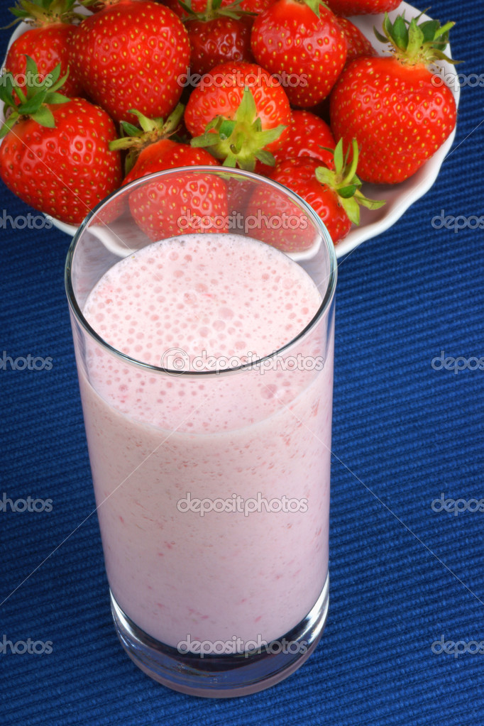 Strawberry milkshake close-up and some fresh strawberries in the background over a blue tablecloth — Stock Photo #11442060