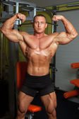 Bodybuilder demonstrating pose in fitness club — Stock Photo