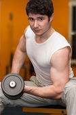 Young man lifting dumbell at fitness gym — Stock Photo