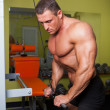 Bodybuilder excercise in fitness club — Stock Photo