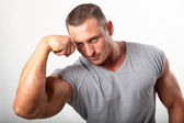 Muscular man flexing his biceps on white — Stock Photo