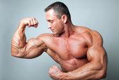 Muskulösen mann beugt seinen bizeps — Stockfoto