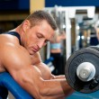 Man with weight training equipment on sport club - Stock Photo
