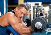 Homem com equipamento de treinamento de peso no clube de esporte — Foto Stock