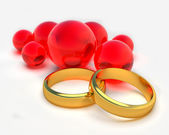 Two gold rings and red balls — Stock Photo