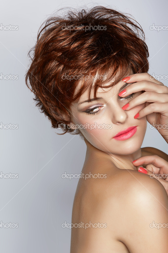 Beautiful woman with short brown hair wears pink lipstick and coral pink manicure on studio background. — Stock Photo #10964827