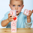 Stock Photo: Boy playing with alphabet blocks