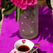 Cup of tea on the background of a bouquet of peonies — Stock Photo