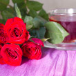 Bouquet of red roses around cups of tea — Stock Photo