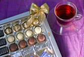 A cup of tea next to a box of sweets — Stock Photo