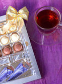 A box of chocolates with a bow around a cup of tea — Stock Photo