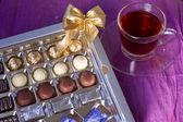 Holiday box of chocolates next cup of tea — Stock Photo