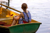 A girl with hair in a braid sits in a boat — Stock Photo