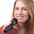 Woman singing into a microphone — Stock Photo