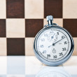 Stopwatch and chessboard — Stock Photo