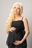 Portrait of the expectant mother in a black dress with polka dot — Stock Photo