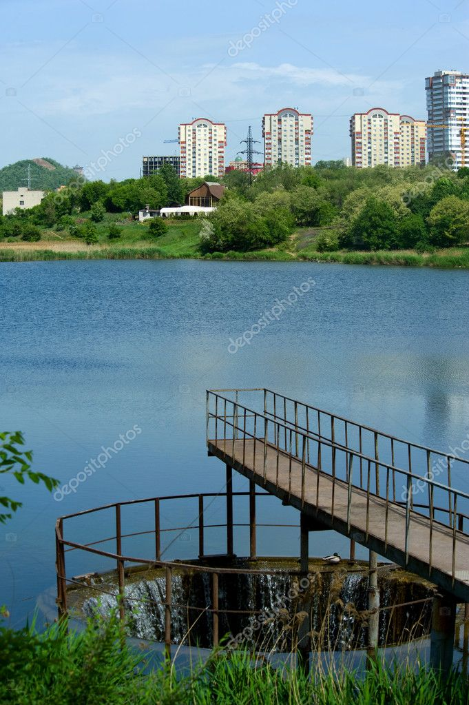 Pond with a bridge on a background of houses and trees in Donetsk — Stock Photo #11104751