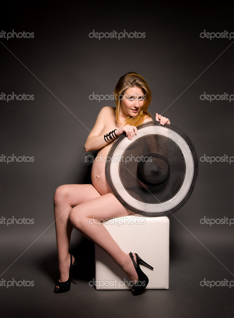 Fashionable topless pregnant woman with wide-brimmed hat on black background — Stock Photo #11477397
