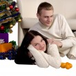 Young couple near the Christmas tree — Stock Photo