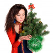 Stock Photo: Beautiful girl is considering jewels on tree