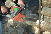 薪のチェーンソーの切口の丸太を持つ男 — ストック写真