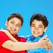 Happy cute boys over blue sky - Stock Photo