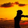 Woman silhouette over sunset — Stock Photo #10763650