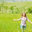 Young happy woman walking on wheat field — Stock Photo #11403813