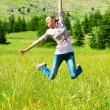 Active sporty woman jumping outdoors — Stock Photo
