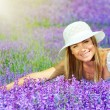 Beautiful happy female lying down on lavender field — Stock Photo