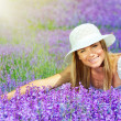 Beautiful happy female lying down on lavender field — Stock Photo #11415151