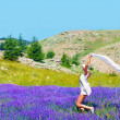 Beautiful girl dancing on lavender field — Stock Photo