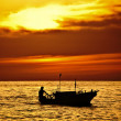 Fisherman on the boat over dramatic sunset — Stock Photo #12010096