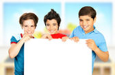 Three boys in classroom holding white clean board — Stock Photo