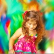 Stock Photo: Adorable small girl dancing over blur colors background