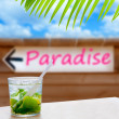 Cocktail mojito in a written paradise word arrow sign — Stock Photo