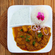 Curry and rice on wooden table with pink flower - Stock Photo