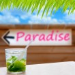 Cocktail mojito in a written paradise word arrow sign - Stock Photo