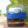 Lorry truck spreading sprinkle water on sand road - Foto Stock
