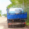 Lorry truck spreading sprinkle water on sand road - Stock Photo