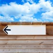 Aged wood arrow direction sign on blue sky - 