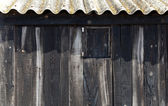 Aged black wood with wavy roof in balearic beach — Stock Photo