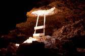 Barbaria cape cave hole with rustic ladder on wood — Stock Photo
