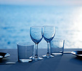 Glass dish cups and glasses on blue sea — Stock Photo