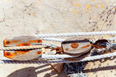 Aged rusted wooden pulley in Mediterrantan port — Stockfoto